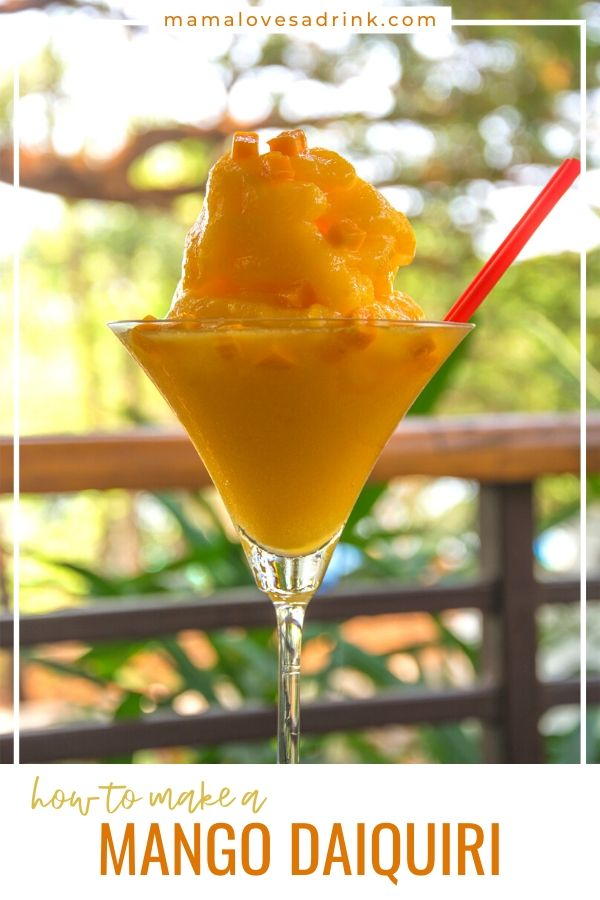 A tall martini glass filled with frozen mango daiquiri