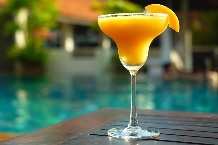 A glass of mango daiquiri with mango garnish against a tropical pool