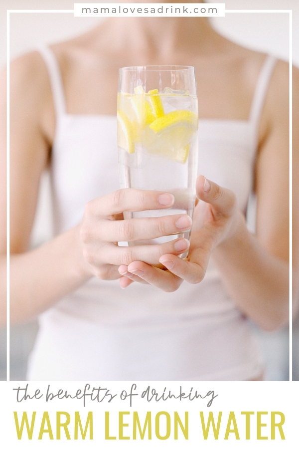 A lady holding a glass of lemon water
