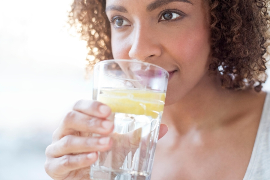 woman drinking a glass of water with lemon slices