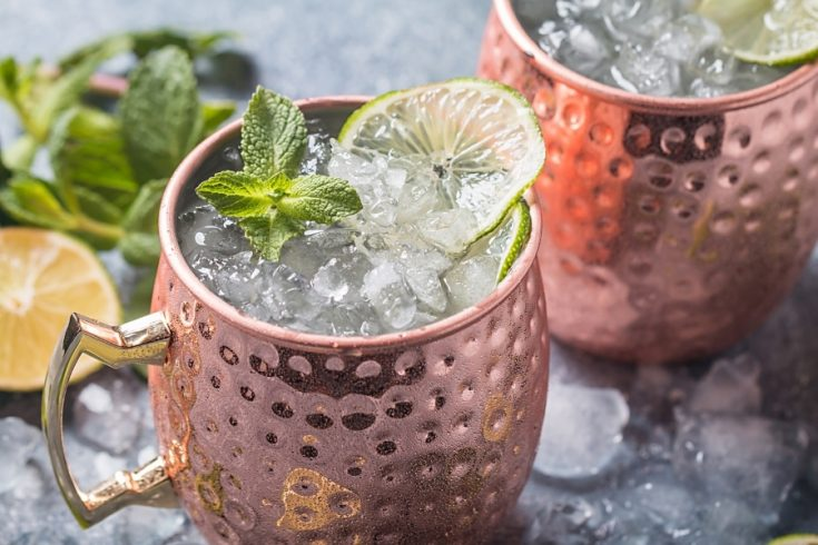 two glasses of refreshing moscow mule cocktails served in coppper cups topped with lots of ice and lime