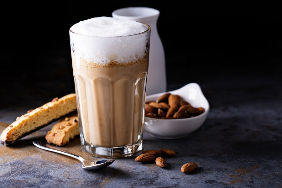 A glass of almond milk coffee with frothed milk